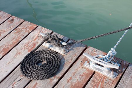 neatly coiled rope leading to the cleat and a moored sailboat photo