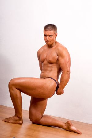 young bodybuilder posing in gym photo