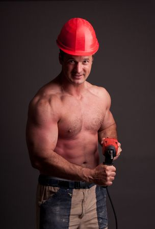 tasker: muscular construction worker with drill Stock Photo