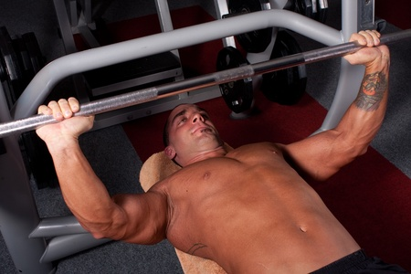Bodybuilder training in the gym -bench press  photo