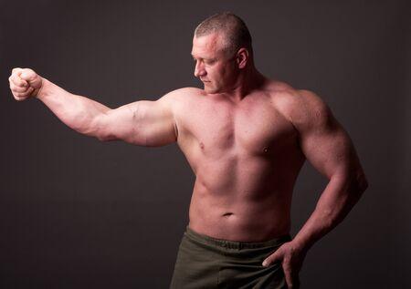 man only: Bodybuilder posing over gray background