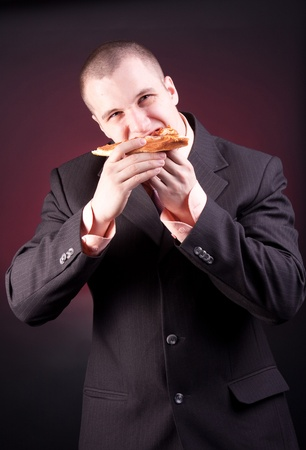 hungry businessman eating a slice pizza photo