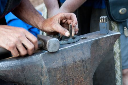 blacksmith working on anvil with hammer photo