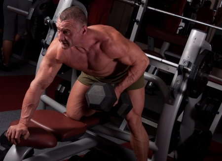 tricep: Bodybuilder exercising in a gym