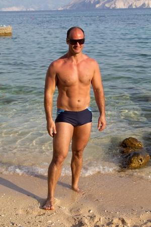 homme muscl� posant dans la plage Banque d'images