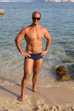 beginner: muscular man  posing in beach Stock Photo
