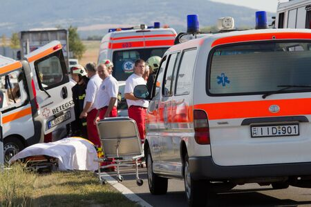 PÉCS, HUNGARY - SEP 15: Firefighters help the victim of car accident on Sep 15, 2011 on Road 6 in Pécs, Hungary.