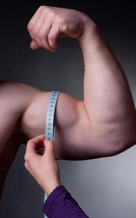 bodybuilder avec un ruban � mesurer autour de son biceps
