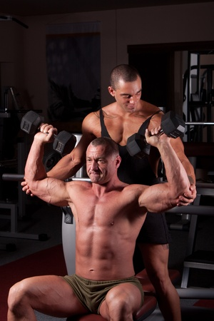nipple: Bodybuilders exercising in a gym together Stock Photo