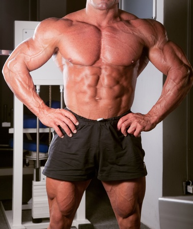 Bodybuilder posiert in der Turnhalle