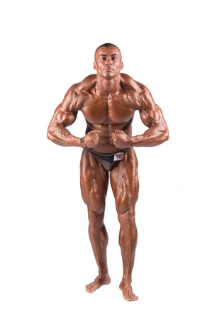athletic body: bodybuilder flexing his muscles in studio Stock Photo