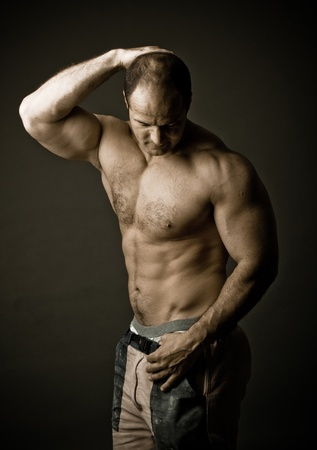 creative strength: mature bodybuilder posing in studio