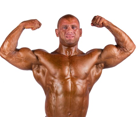 tanned body: bodybuilder flexing his muscles in studio Stock Photo