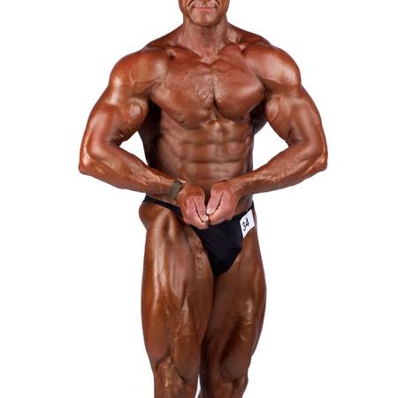 bodybuilder flexing his muscles in studio photo