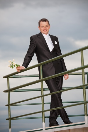 young groom with cloudy sky photo