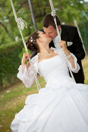beautiful young wedding couple riding on a swing photo
