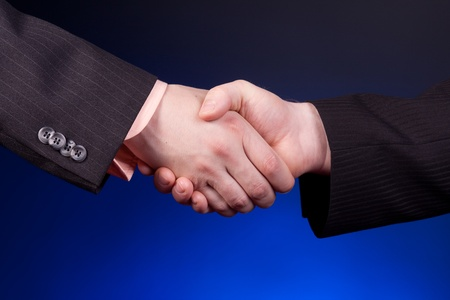 two businessman shaking hands over blue background