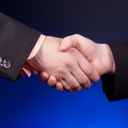 two businessman shaking hands over blue background photo