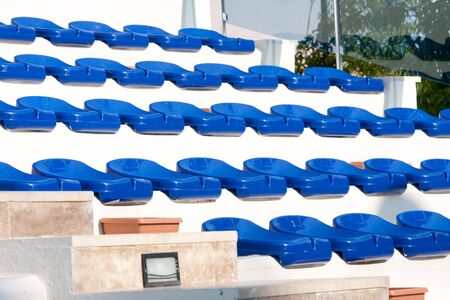 colorful plastic chairs in a stadium photo