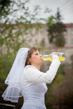 beautiful young bride drinking orange juice photo