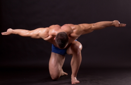Bodybuilder posing in studio, flexing his lats Stock Photo - 14626111