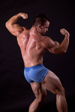 Bodybuilder posing in studio, flexing his lats photo
