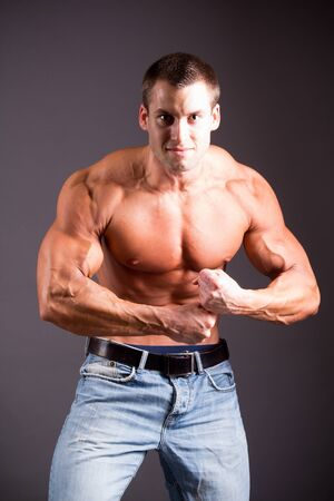 young muscular man flexing his muscles Stock Photo - 15029642