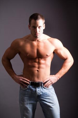 jeune homme muscl� fl�chissant ses muscles