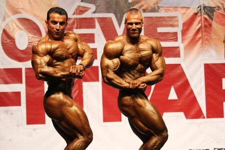 BUDAPEST - OCTOBER 21: Mahali Ayari (left) and Molnar Peter (right) participates in Fitparade bodybuilding championship Open -100 kg category on October 21, 2012 in Budapest, Hungary