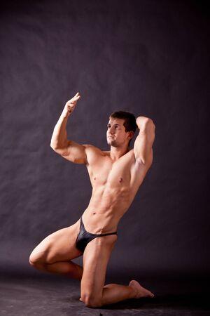 tricep: young bodybuilder posing in studio