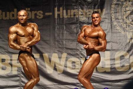 BUDAORS, HUNGARY - JUNE 10: Ivan Rapakov (left) and Benjamin Bochoda (right) participates in WBPF bodybuilding World Cup Junior category on June 10, 2012 in Budaors, Hungary
