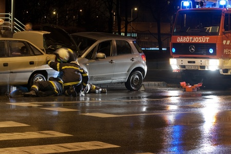 negligent: PECS, HUNGARY - DEC. 01: car crashed. Firefighter try to help the victim of car accident on Dec. 01, 2011 on Road 6 in Pecs, Hungary.