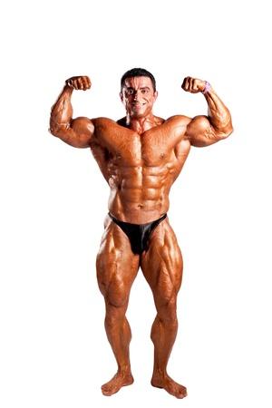 cuerpo hombre: fisicoculturista flexionando sus m?sculos en el estudio
