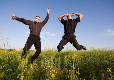 young businessmans jumping in rapeseed Stock Photo