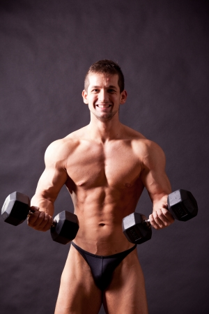 young bodybuilder traininig over balck background Stock Photo - 17447060