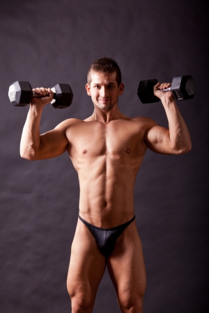 young bodybuilder traininig over balck background Stock Photo - 17447059