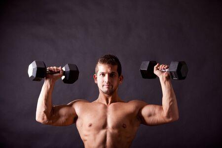 young bodybuilder traininig over balck background Stock Photo - 17447054