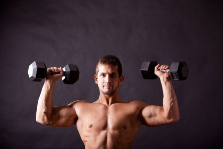 young bodybuilder traininig over balck background Stock Photo - 17447054
