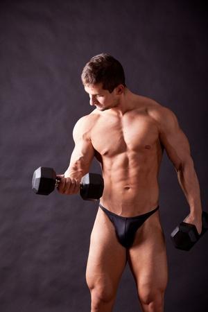 sixpacks: young bodybuilder traininig over balck background