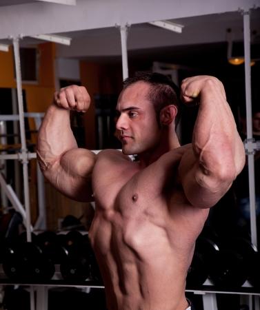 muskeltraining: Bodybuilder posiert in der Turnhalle