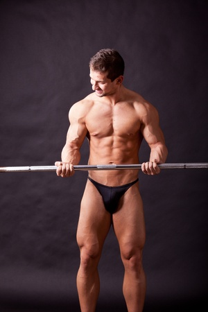 pectorals: young bodybuilder traininig over balck background