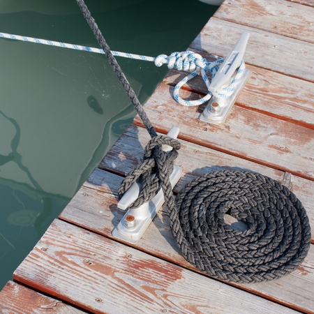cleat: neatly coiled rope leading to the cleat Stock Photo