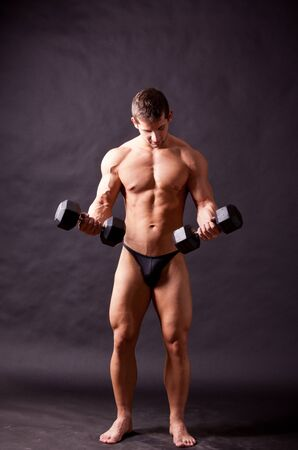 young bodybuilder traininig over balck background photo