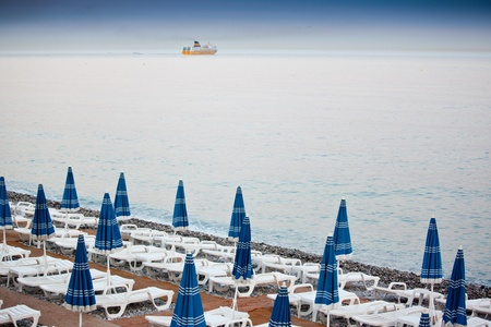Row of beach umbrellas in a beach resort of Nice photo