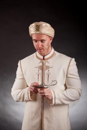 lampada magica: Giovane uomo in costume orientale con lampada magica
