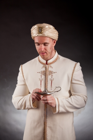 Young man in oriental costume with magic lamp photo
