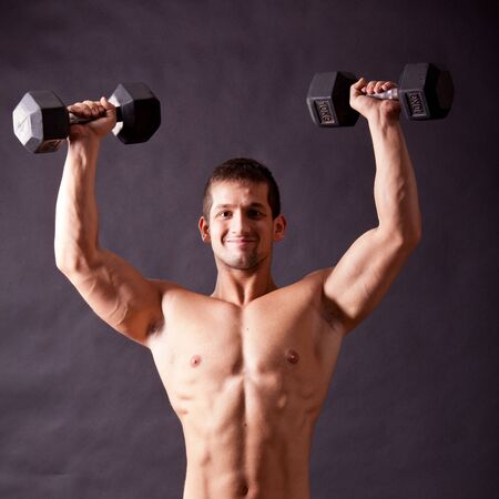 young bodybuilder traininig over balck background