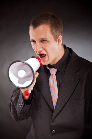 businessman shouting through megaphone in studio Stock Photo - 21232937