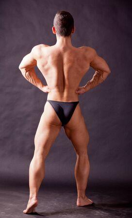 sixpacks: young bodybuilder posing in studio