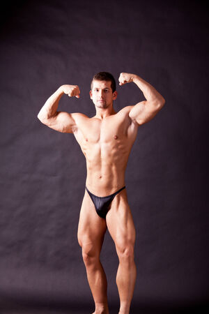 pectorals: young bodybuilder posing in studio